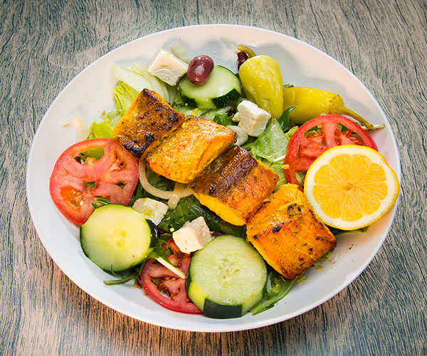 Salmon salad with lemon, tomatoes, and lettuce